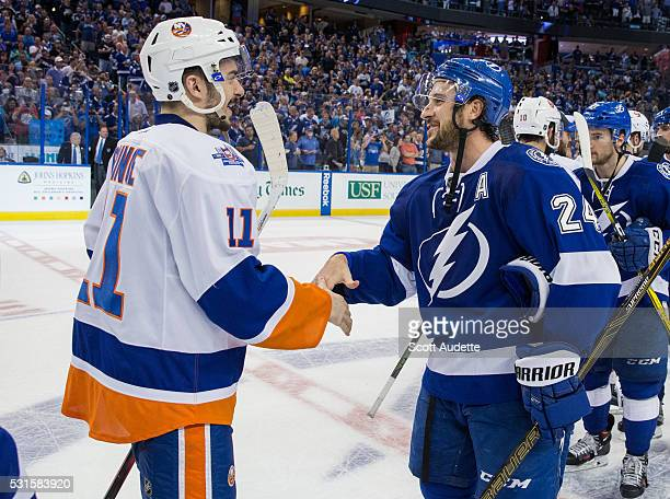 Ryan Callahan of the Tampa Bay Lightning celebrates the series win and shakes hands with Shane Prince of the New York Islanders after Game Five of...