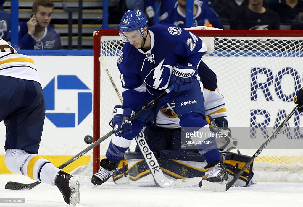 Ryan Callahan #24 of the Tampa Bay Lightning tries to deflect the puck past goalie Jhonas Enroth #1 of the Buffalo Sabres at the Tampa Bay Times Forum on March 6, 2014 in Tampa, Florida.