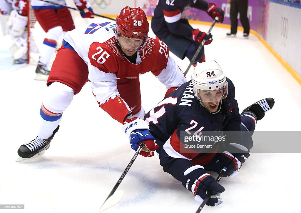 Ryan Callahan of the United States falls to the ice after tangling with Vyacheslav Voynov of Russia during the Men's Ice Hockey Preliminary Round...