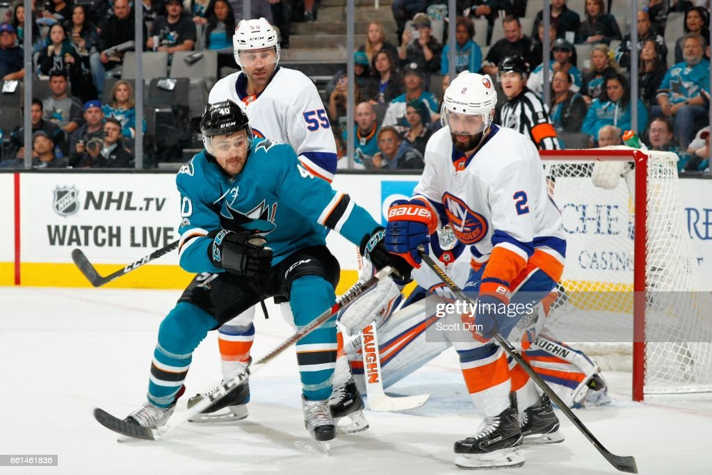 Ryan Carpenter #40 of the San Jose Sharks and Nick Leddy #2 of the New York Islanders battle for the puck at SAP Center on October 14, 2017 in San Jose, California.