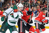 Ryan Carter of the Minnesota Wild and Michal Rozsival of the Chicago Blackhawks watch for the puck during the NHL game at the United Center on...