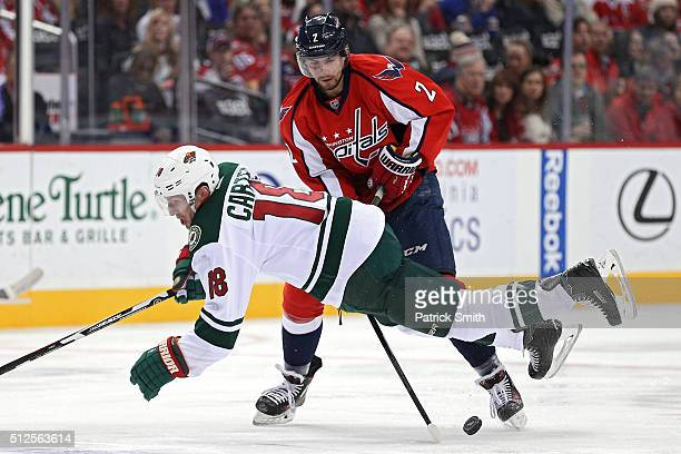 Ryan Carter of the Minnesota Wild is tripped up by Matt Niskanen of the Washington Capitals during the third period at Verizon Center on February 26...