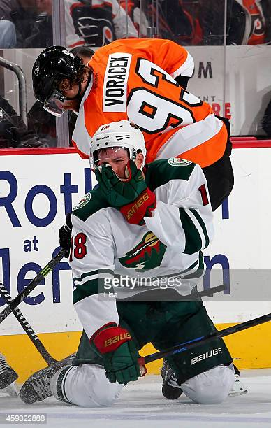Ryan Carter of the Minnesota Wild reacts after he got a stick in his face as Jakub Voracek of the Philadelphia Flyers fights for the puck on November...