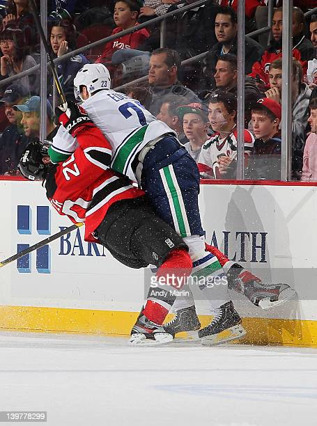 Ryan Carter of the New Jersey Devils is checked hard near the boards by Alexander Edler of the Vancouver Canucks during the game at the Prudential...