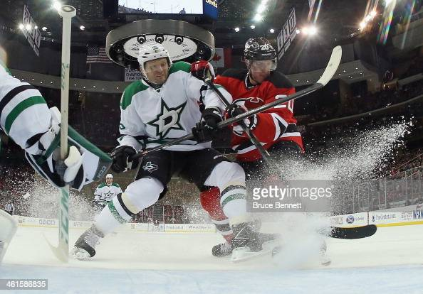 Ryan Carter of the New Jersey Devils is held back by Sergei Gonchar of the Dallas Stars during the second period at the Prudential Center on January...
