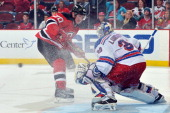 Ryan Carter of the New Jersey Devils sprays Henrik Lundqvist of the New York Rangers with ice as he makes a save at the Prudential Center on October...