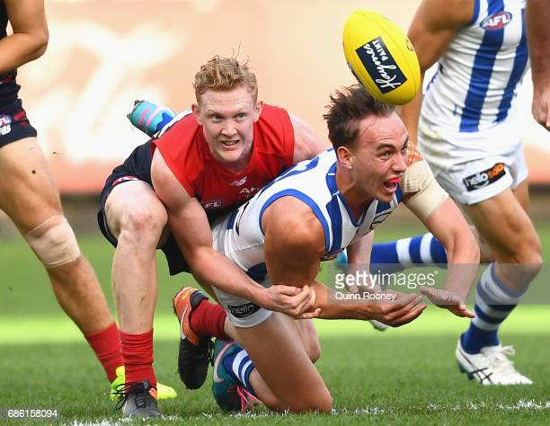 Ryan Clarke of the Kangaroos handballs whilst being tackled by Clayton Oliver of the Demons during the round nine AFL match between the Melbourne...