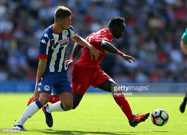Ryan Colclough of Wigan Athletic challenges Sadio Mane of Liverpool during the PreSeason Friendly match between Wigan Athletic and Liverpool at JJB...