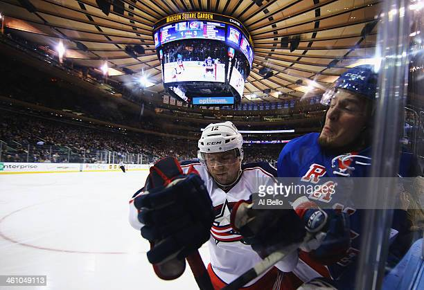 Ryan Craig of the Columbus Blue Jackets checks JT Miller of the New York Rangers during their game at Madison Square Garden on January 6 2014 in New...