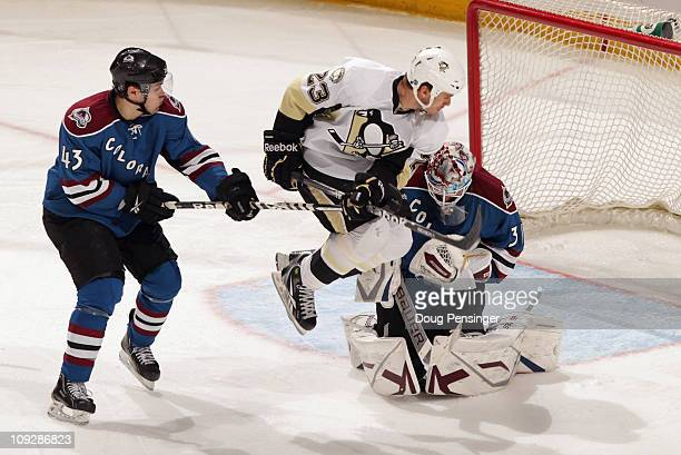 Ryan Craig of the Pittsburgh Penguins jumps to screen a shot as Cameron Gaunce of the Colorado Avalanche as defends and goalie Peter Budaj of the...
