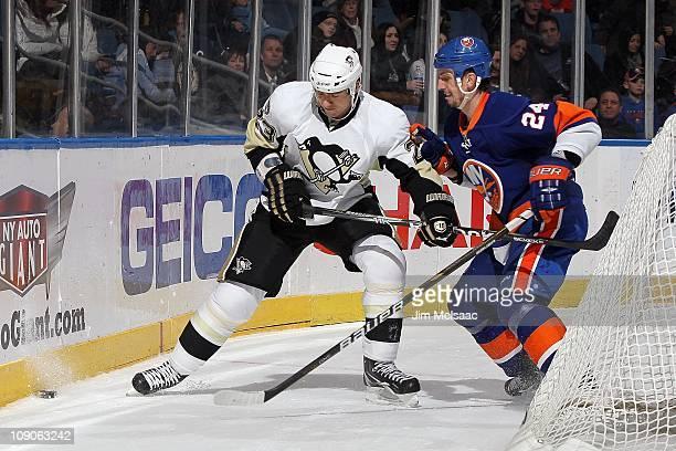 Ryan Craig of the Pittsburgh Penguins skates against Radek Martinek of the New York Islanders on February 11 2011 at Nassau Coliseum in Uniondale New...