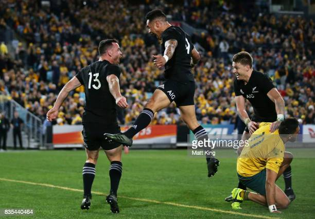Ryan Crotty of the All Blacks celebrates with team mates Aaron Smith and Beauden Barrett after scoring a try during The Rugby Championship Bledisloe...
