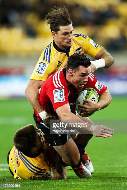 Ryan Crotty of the Crusaders is tackled by Beauden Barrett and Cory Jane of the Hurricanes during the round 12 Super Rugby match between the...