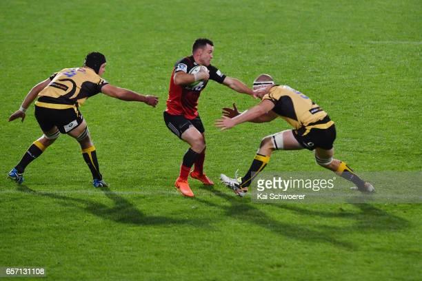 Ryan Crotty of the Crusaders is tackled by Ross HaylettPetty of the Force and Matt Philip of the Force during the round five Super Rugby match...