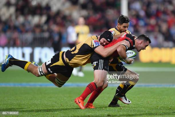 Ryan Crotty of the Crusaders is tackled by Ross HaylettPetty of the Force during the round five Super Rugby match between the Crusaders and the Force...