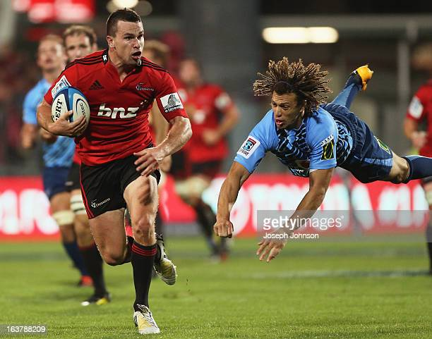 Ryan Crotty of the Crusaders with the ball with Zane Kirchner of the Bulls missing a dive tackle during the round five Super Rugby match between the...