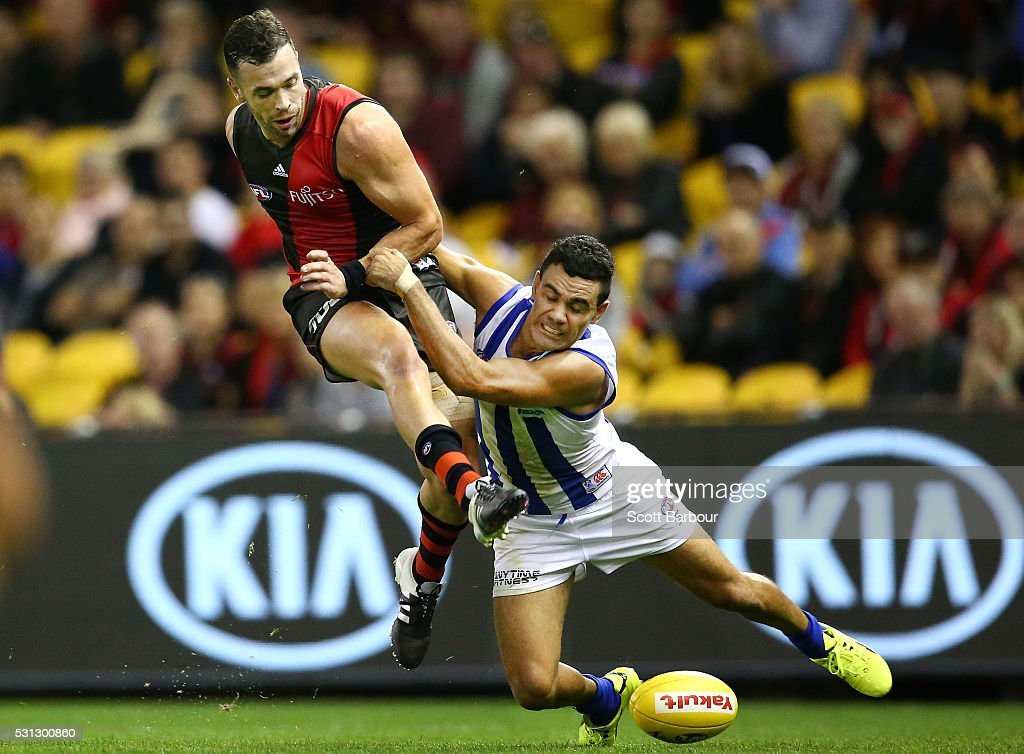 Ryan Crowley of the Bombers is tackled by Lindsay Thomas of the Kangaroos during the round eight AFL match between the Essendon Bombers and the North Melbourne Kangaroos at Etihad Stadium on May 14, 2016 in Melbourne, Australia.