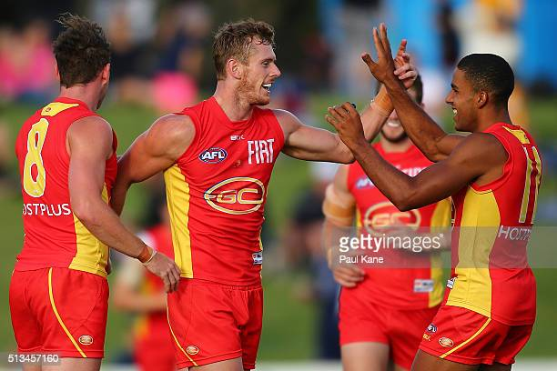 Ryan Davis of the Suns celebrates a goal with team mates during the 2016 AFL NAB Challenge match between the West Coast Eagles and the Gold Coast...