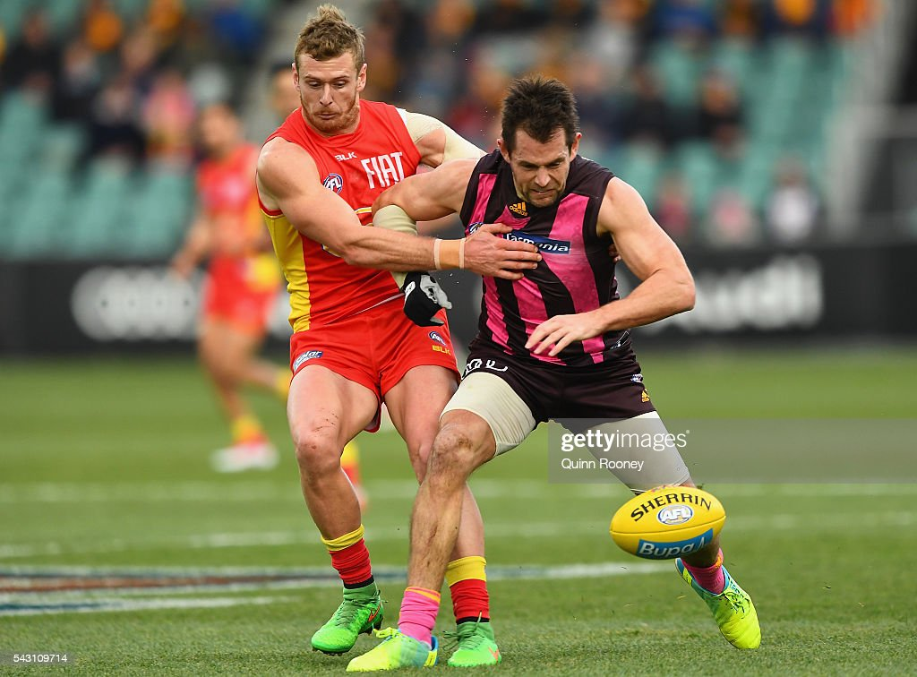 Ryan Davis of the Suns is bumped by <a gi-track='captionPersonalityLinkClicked' href=/galleries/search?phrase=Luke+Hodge&family=editorial&specificpeople=241521 ng-click='$event.stopPropagation()'>Luke Hodge</a> of the Hawks during the round 14 AFL match between the Hawthorn Hawks and the Gold Coast Suns at Aurora Stadium on June 26, 2016 in Launceston, Australia.