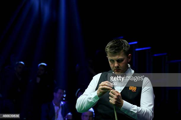 Ryan Day of UK chalks his cue against Mark J Williams of UK during day two of the 2015 Snooker World Grand Prix at Venue Cymru on March 17 2015 in...