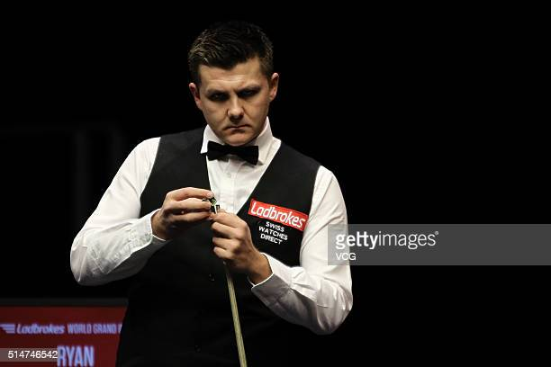 Ryan Day of Wales chalks his cue in the second round match against John Higgins of Scotland on day three of the Ladbrokes World Grand Prix at Venue...