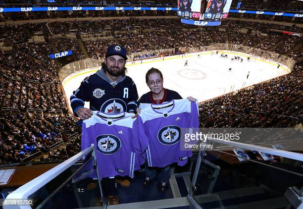 Ryan Delong and Leslie Mackay pose with Hockey Fights Cancer jerseys given on behalf of the Winnipeg Jets during a first period stoppage in play...