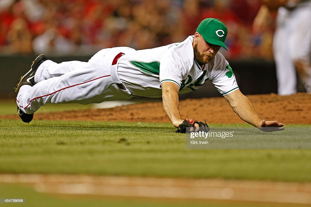 Ryan Dennick #41 of the Cincinnati Reds dives to field a ground ball hit by Matt den Dekker #6 of the New York Mets during the sixth inning at Great American Ball Park on September 5, 2014 in Cincinnati, Ohio. New York defeated Cincinnati 14-5.