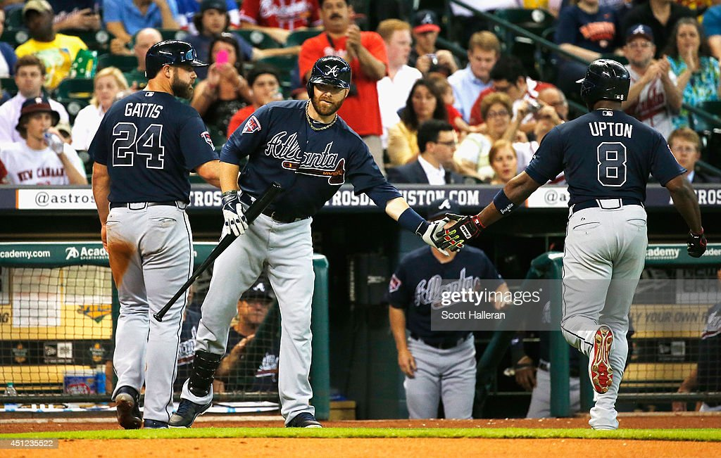 Ryan Doumit (C) #4 of the Atlanta Braves greets Evan Gattis #24 and Justin Upton #8 after Upton hit a sacrifice fly to score Gattis in the second inning of their game against the Houston Astros at Minute Maid Park on June 25, 2014 in Houston, Texas.