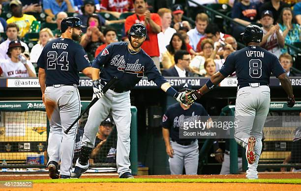 Ryan Doumit of the Atlanta Braves greets Evan Gattis and Justin Upton after Upton hit a sacrifice fly to score Gattis in the second inning of their...