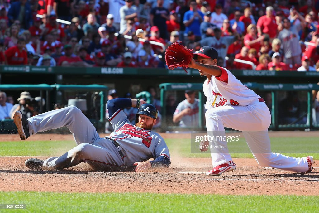 Ryan Doumit of the Atlanta Braves scores the gamewinning run on a wild pitch by reliever Carlos Martinez of the St Louis Cardinals in the ninth...