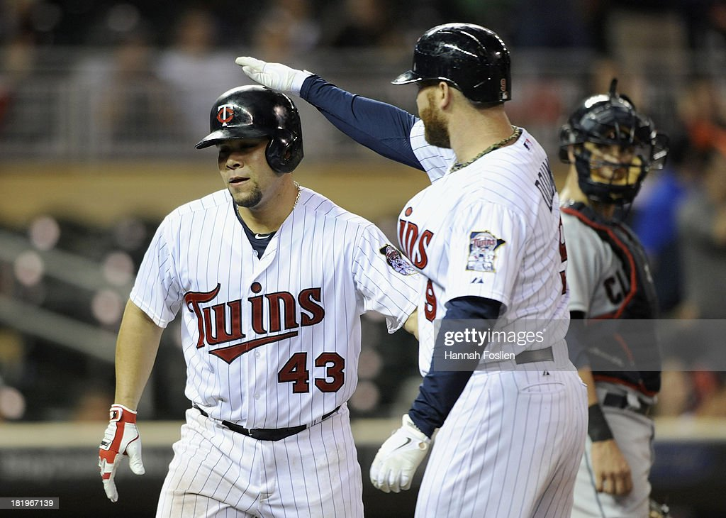<a gi-track='captionPersonalityLinkClicked' href=/galleries/search?phrase=Ryan+Doumit&family=editorial&specificpeople=598785 ng-click='$event.stopPropagation()'>Ryan Doumit</a> #9 of the Minnesota Twins congratulates teammate Josmil Pinto #43 as <a gi-track='captionPersonalityLinkClicked' href=/galleries/search?phrase=Yan+Gomes&family=editorial&specificpeople=9004037 ng-click='$event.stopPropagation()'>Yan Gomes</a> #10 of the Cleveland Indians looks on after Pinto's two-run home run in the ninth inning of the game on September 26, 2013 at Target Field in Minneapolis, Minnesota. The Indians defeated the Twins 6-5.