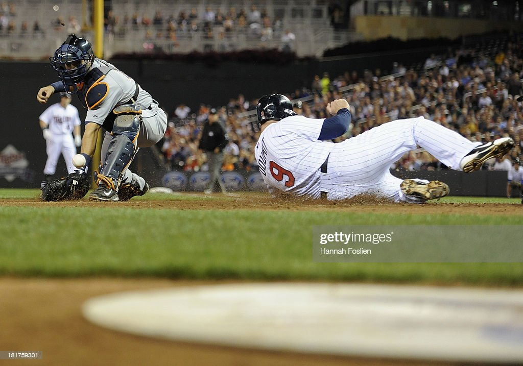 Ryan Doumit #9 of the Minnesota Twins slides safely at home plate as the baseball gets past Alex Avila #13 of the Detroit Tigers during the second inning of the game on September 24, 2013 at Target Field in Minneapolis, Minnesota.