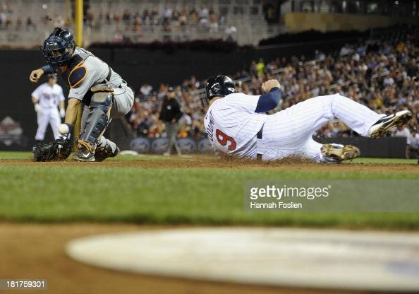 Ryan Doumit of the Minnesota Twins slides safely at home plate as the baseball gets past Alex Avila of the Detroit Tigers during the second inning of...