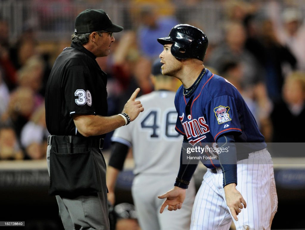 Ryan Doumit #18 of the Minnesota Twins speaks with home plate umpire Paul Nauert #39 after being called out at home plate during the fourth inning of the game against the New York Yankees on September 24, 2012 at Target Field in Minneapolis, Minnesota.