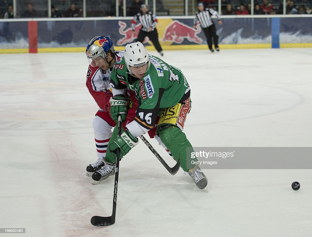 Ryan Duncan of Salzburg (left) challenges Ales Music of Ljubljana during the Erste Bank Eishockey Liga match between EC Red Bull Salzburg and HDD TELEMACH Olimpija Ljubljana at Eisarena Salzburg on December 9, 2012 in Salzburg, Austria.
