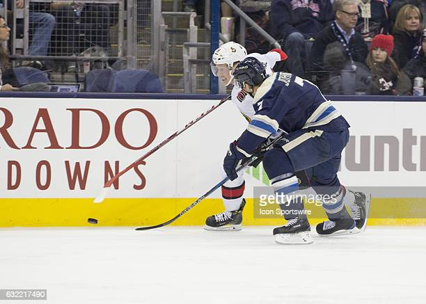 Ryan Dzingel of the Ottawa Senators and Jack Johnson of the Columbus Blue Jackets battle for the puck along the boards during the second period of...