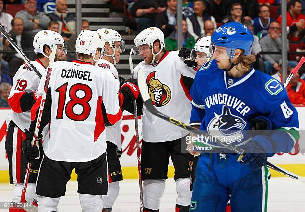 Ryan Dzingel of the Ottawa Senators is congratulated by teammates after scoring as Philip Larsen of the Vancouver Canucks looks on dejected during...