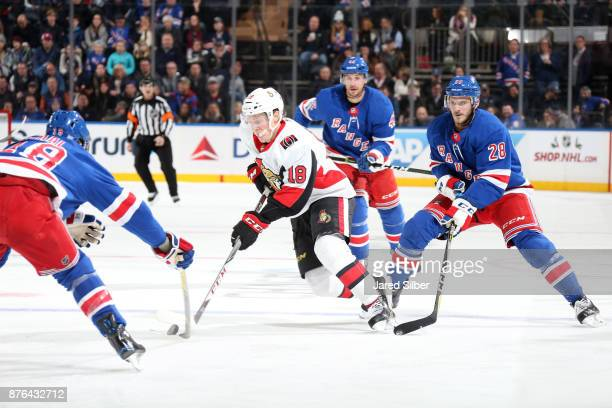 Ryan Dzingel of the Ottawa Senators skates with the puck against Marc Staal and Paul Carey of the New York Rangers at Madison Square Garden on...