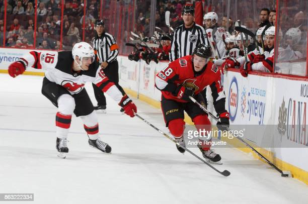 Ryan Dzingel of the Ottawa Senators stickhandles the puck against Steven Santini the New Jersey Devils at Canadian Tire Centre on October 19 2017 in...