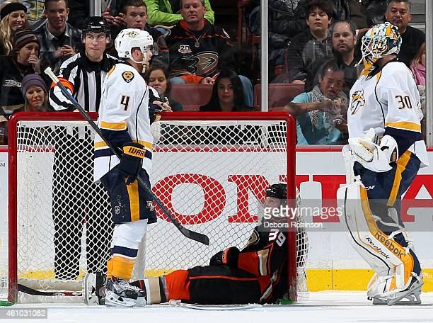 Ryan Ellis and Carter Hutton of the Nashville Predators talk as Matt Beleskey of the Anaheim Ducks looks on while sitting inside the net on January 4...