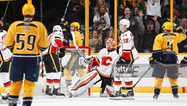 Ryan Ellis and Colin Wilson of the Nashville Predators celebrate a goal against Chad Johnson of the Calgary Flames during an NHL game at Bridgestone...
