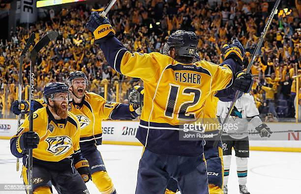 Ryan Ellis and Mattias Ekholm celebrate with Mike Fisher of the Nashville Predators after his game winning third overtime goal against the San Jose...