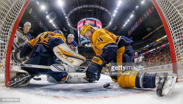 Ryan Ellis makes a save in the crease with Pekka Rinne of the Nashville Predators against Vladimir Tarasenko Jaden Schwartz of the St Louis Blues in...