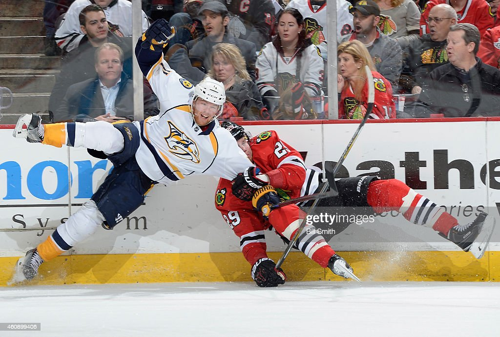 Ryan Ellis #4 of the Nashville Predators and Bryan Bickell #29 of the Chicago Blackhawks collide by the boards during the NHL game at the United Center on December 29, 2014 in Chicago, Illinois.