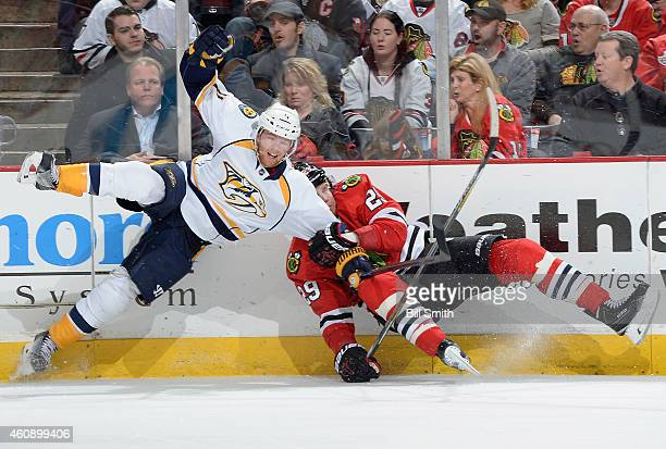 Ryan Ellis of the Nashville Predators and Bryan Bickell of the Chicago Blackhawks collide by the boards during the NHL game at the United Center on...