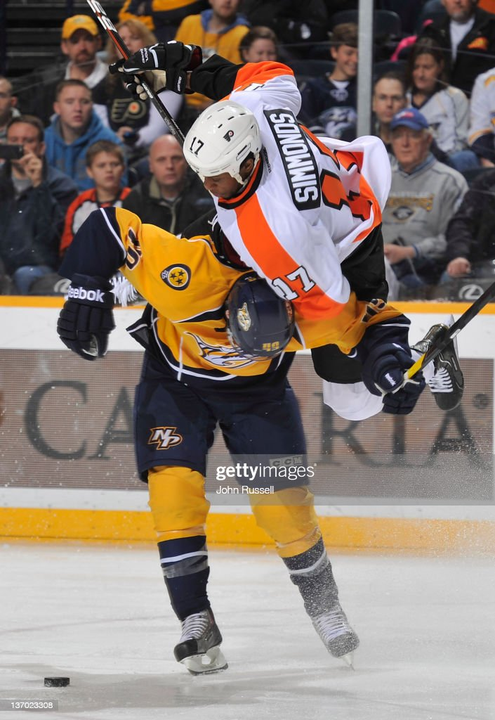 Ryan Ellis #49 of the Nashville Predators checks Wayne Simmonds #17 the Philadelphia Flyers off the puck during an NHL game at the Bridgestone Arena on January 14, 2012 in Nashville, Tennessee.
