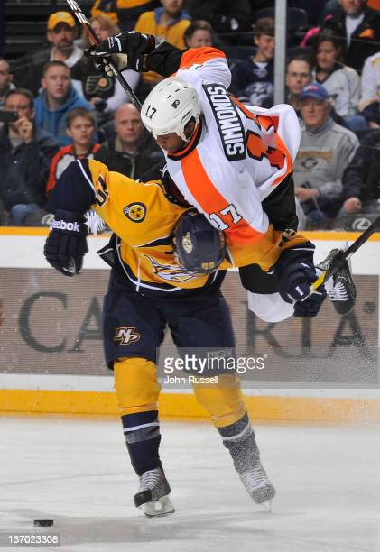 Ryan Ellis of the Nashville Predators checks Wayne Simmonds the Philadelphia Flyers off the puck during an NHL game at the Bridgestone Arena on...
