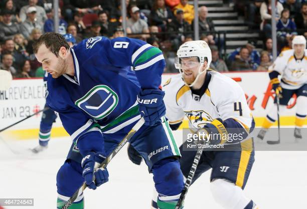 Ryan Ellis of the Nashville Predators checks Zack Kassian of the Vancouver Canucks during their NHL game at Rogers Arena January 23 2014 in Vancouver...