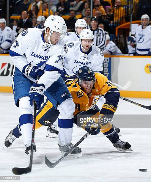 Ryan Ellis of the Nashville Predators dives for the puck against Victor Hedman of the Tampa Bay Lightning at Bridgestone Arena on February 27 2014 in...