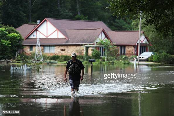 Ryan Evans walks along a flooded road on August 15 2016 in Baton Rouge Louisiana Recordbreaking rains pelted Louisiana over the weekend leaving the...